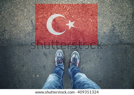 Point of view of a person legs standing in front of Turkey Flag painted on city asphalt street ground. - stock photo