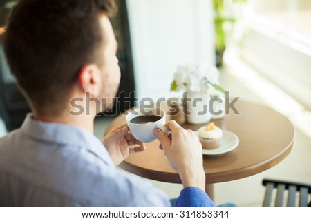 Point of view of a young man enjoying a cup of coffee by himself in a cafe