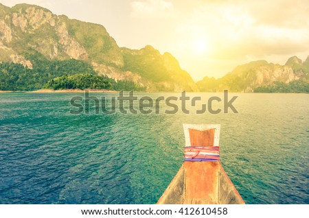 Point of view of Cheow Lan lake from long tail boat - Khao Sok National Park in Thailand - Adventure travel concept with wanderlust feelings - Enhanced sunflare halo with vivid vintage filter - stock photo