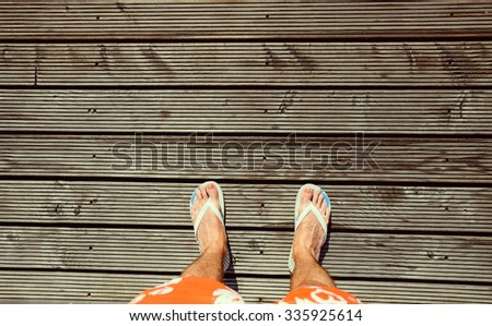 Point of view of young man, he is looking on his feet wearing in flip-flops and standing on wooden floor, close up - stock photo