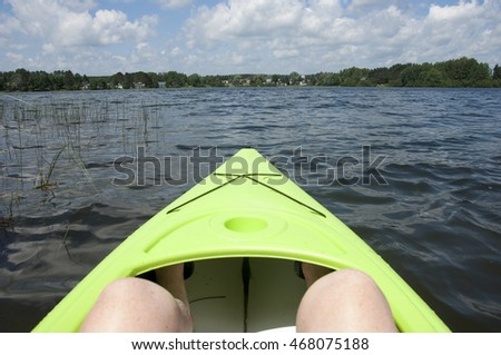 Point of view (POV)  from a caucasian girl with freckled legs sitting in a green kayak looking across Lac de Source at the vacation homes and trees in Mont Laurier, Quebec, Canada.