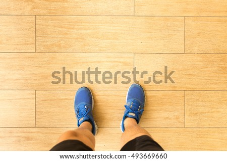 Point of view shot of a runner man look down to his feet on the wooden floor