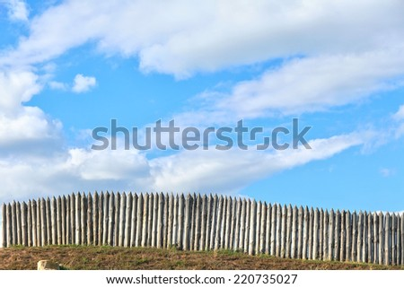 pointed palisade against the blue sky and white clouds on a sunny summer day