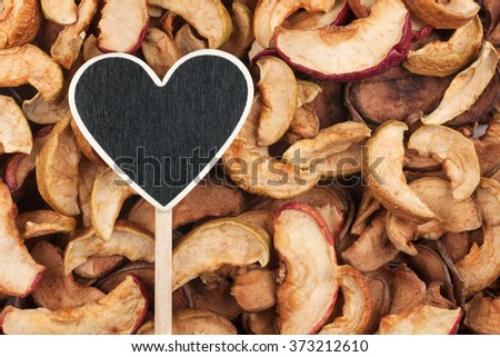 Pointer in the form of heart lies on dry apple, with space for your text - stock photo