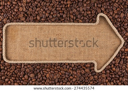 Pointer made from rope with  coffee beans  lying on sackcloth, with space for your text - stock photo