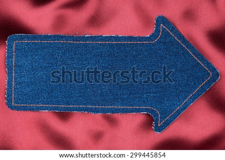 Pointer made of denim fabric with yellow stitching on red silk, with space for your text - stock photo