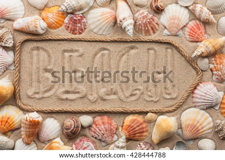 Pointer made of rope with an inscription BEACH, with sea shells, on sand - stock photo