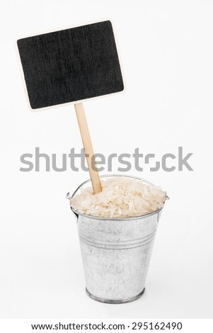 Pointer, price in bucket of  rice grains, on a white background - stock photo