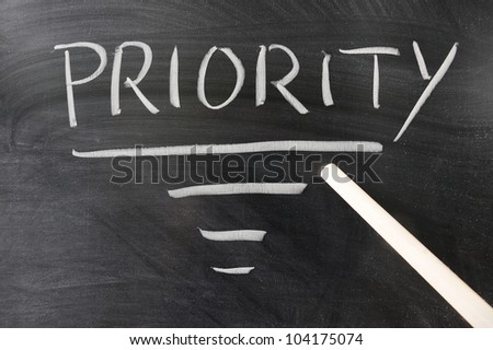 Pointer stick points to Priority word written on the blackboard - stock photo