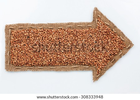 Pointer with buckwheat grains, on white background - stock photo