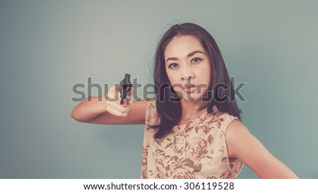 Pointing a gun to the camera. Vintage, retro style of portrait of Asian woman in pink vintage dress on blue - green background. - stock photo