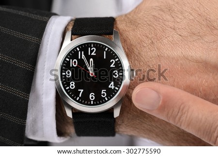 Pointing at time on wristwatch - stock photo