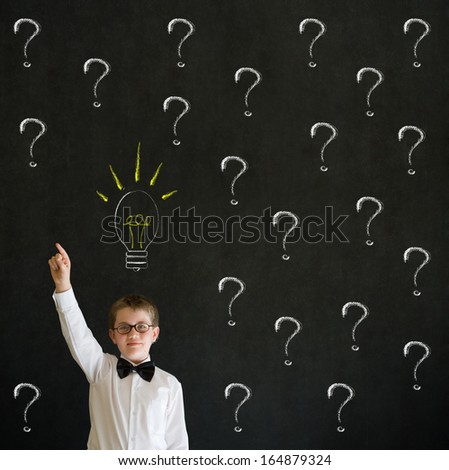Pointing boy dressed up as business man questioning ideas on blackboard background - stock photo