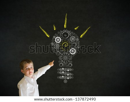 Pointing boy dressed up as business man with bright idea gear cog lightbulb on blackboard background - stock photo