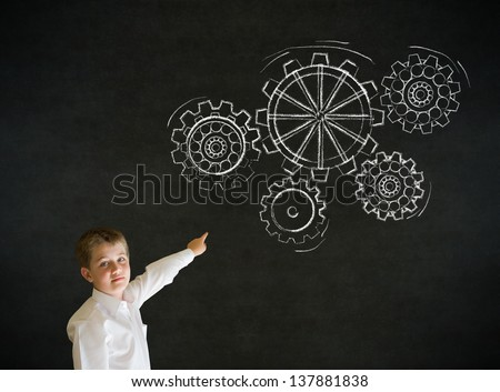 Pointing boy dressed up as business man with chalk turning gear cogs or gears on blackboard background - stock photo