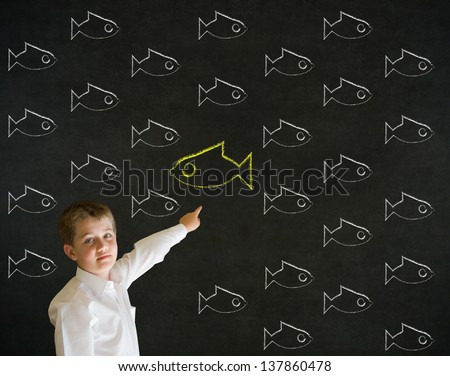 Pointing boy dressed up as business man with independent thinking chalk fish swimming against the flow on blackboard background - stock photo