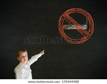 Pointing boy dressed up as business man with no smoking chalk sign on blackboard background - stock photo