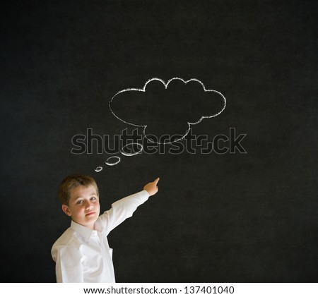 Pointing boy dressed up as business man with thought thinking chalk cloud on blackboard background - stock photo