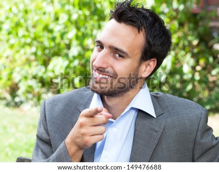 Pointing businessman in the park  - stock photo