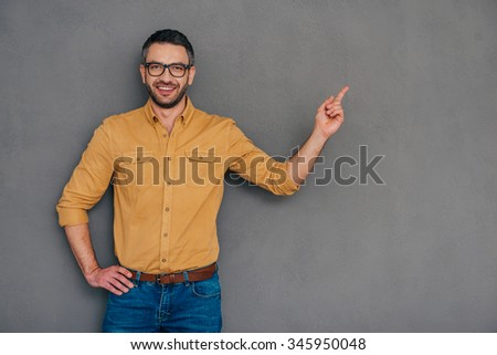 Pointing copy space. Confident mature man pointing away and smiling while standing against grey background - stock photo