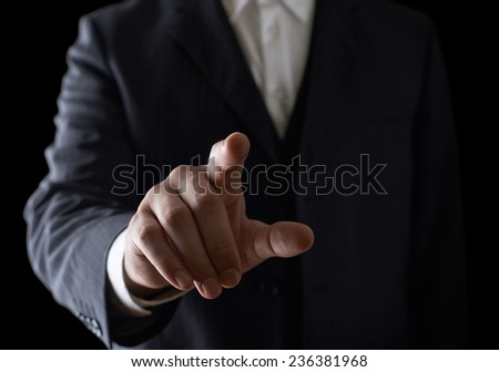Pointing finger close-up shot of a caucasian man in a business suit, low-key dramatic light composition - stock photo
