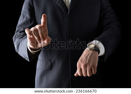 Pointing finger while showing time with the other hand close-up shot of a caucasian man in a business suit, low-key dramatic light composition - stock photo