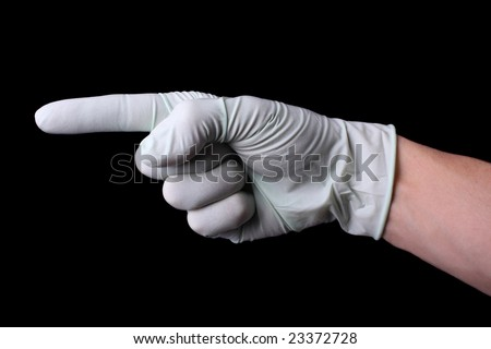 Pointing hand in medical glove - stock photo