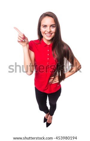 Pointing showing woman. Humorous high angle studio portrait of a grinning woman pointing to the left of the frame with her finger.  - stock photo