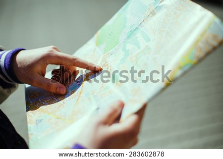 Pointing the finger at a map at sunny day, close-up - stock photo