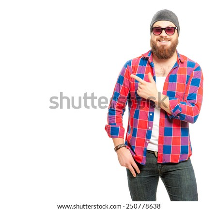 Pointing your product. Portrait of handsome bearded man in casual shirt and sunglasses pointing copy space and smiling while standing against white background - stock photo