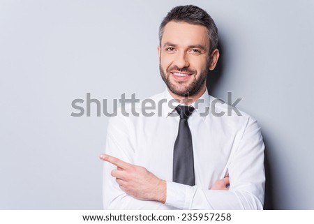Pointing your product. Portrait of handsome mature man in shirt and tie pointing copy space and smiling while standing against grey background - stock photo