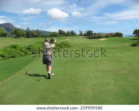POIPU, USA-February 25, 2008: A senior golfer tees off at a golf course on the island of Kauai.  Golf is a favorite activity of retired people visiting the island. - stock photo
