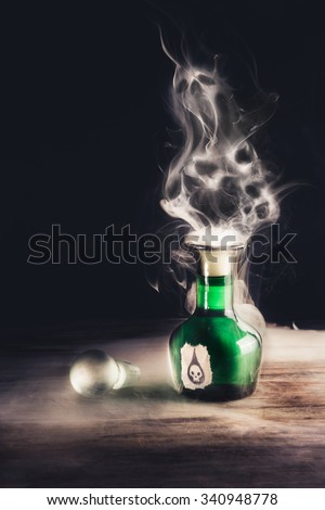 poison bottle on a wooden surface with skulls made of smoke - stock photo