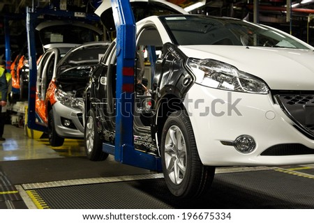 POISSY, FRANCE - JANUARY 27, 2012 - Assembly line  of cars Peugeot 207 and 208 at the Poissy factory of PSA Peugeot Citroen. - stock photo