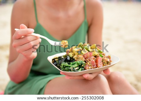 Poke bowl salad plate. A traditional local Hawaii food dish with raw marinated ahi yellowfin tuna fish. Woman sitting on beach eating lunch. - stock photo