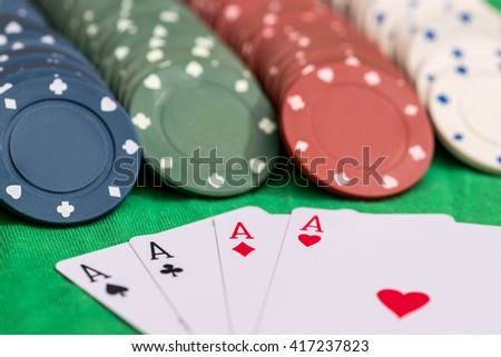 poker aces with chip on green table