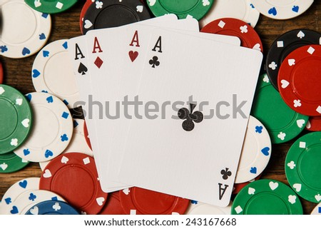 Poker cards and chips on wooden surface