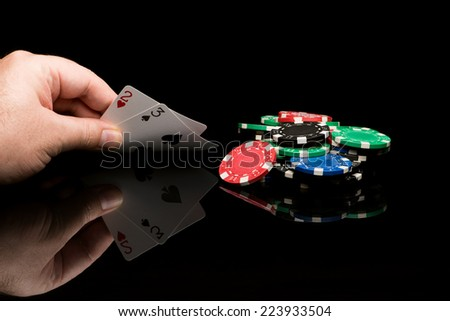 Poker cards with hand on black background with reflexion