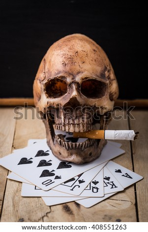 poker cards with model skull on wooden floor