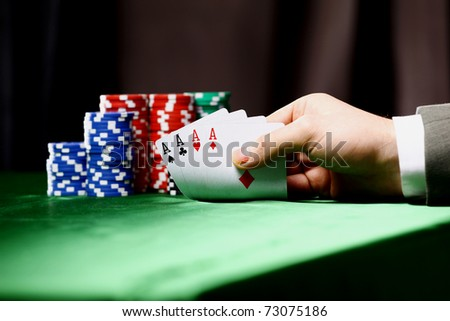 Poker chips and a hand flip the cards isolated against green felt - stock photo