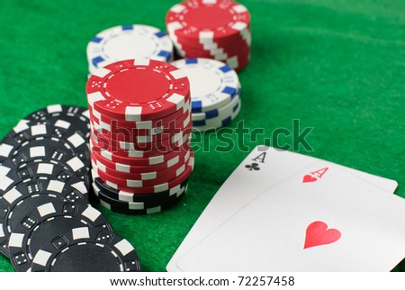 Poker chips and cards isolated against green felt - stock photo