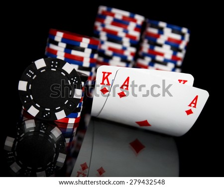 Poker chips and cards isolated on black background - stock photo