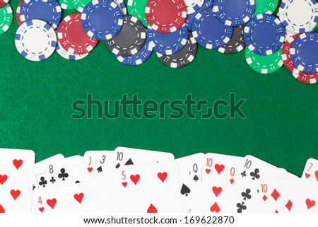 poker chips and cards on a green casino table background - stock photo