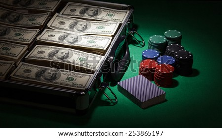 Poker chips and dollar bills in case on green background