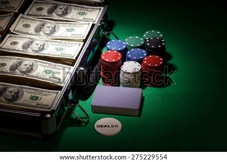 Poker chips and dollar bills in case on green background - stock photo
