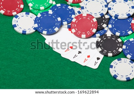 poker chips and four aces on a green casino table background - stock photo