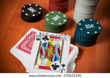 Poker chips and generic playing cards. Courts for poker chips and dice on wooden table