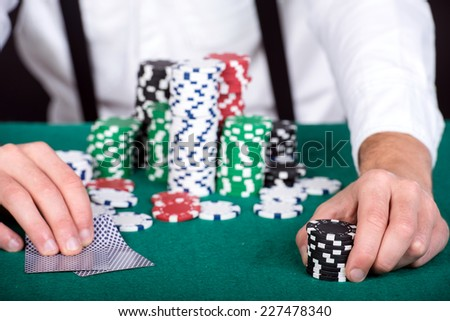 Poker chips and playing cards in hands above it on a green table.