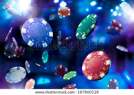 Poker Chips falling with dramatic lighting - stock photo