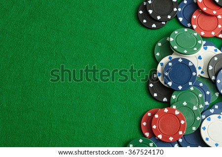 Poker chips forming a border on the right with a green  background - stock photo